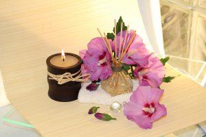 Die Ayurveda-Diät bietet entspannende Element mit Massagen und Yoga. Hier sehen sie eine Duftkerze, Duftstäbchen und rosa Blüten