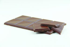 Tipps für die Ernährung, ein kleines Stück schwarzer Schokolade kann auch bei einer Diät glücklich machen und Frust vermeiden.